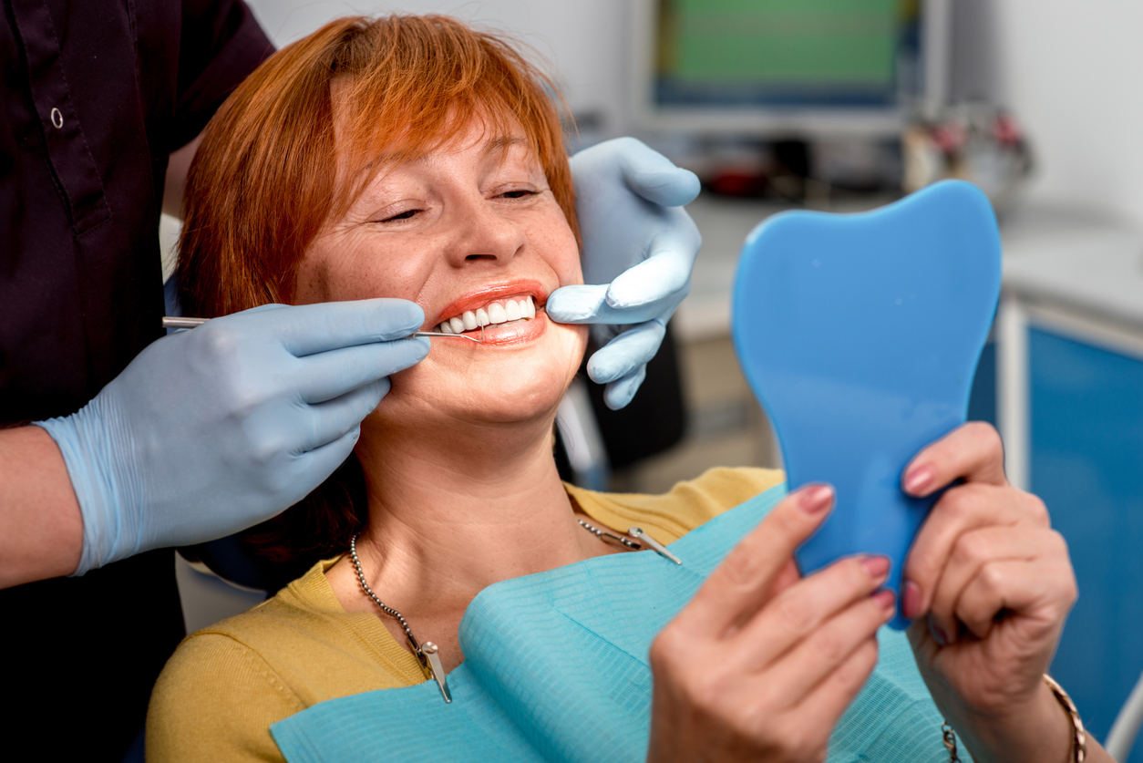 Smiling woman in dentist chair looking at whether dental implants are better than dentures in mirror with dentist