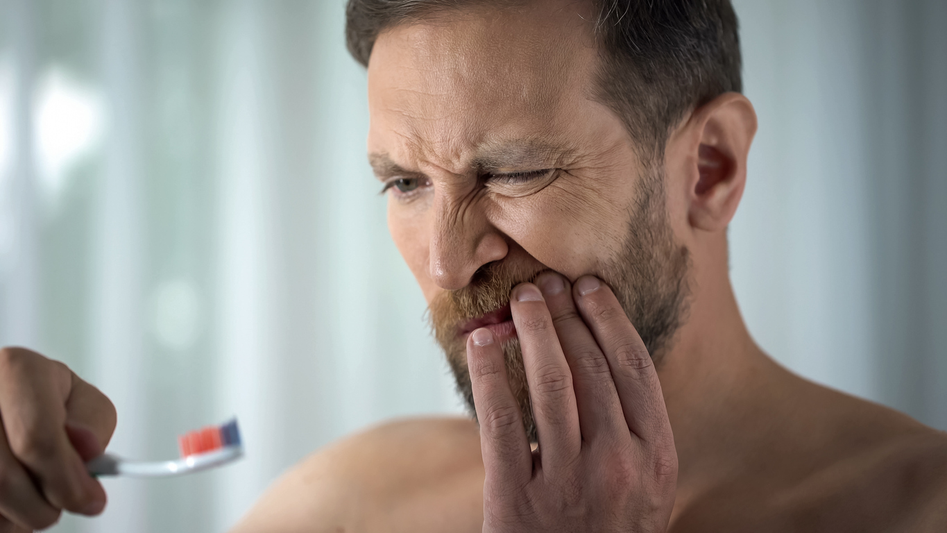 Man with sore gums looking at toothbrush asking why do gums bleed